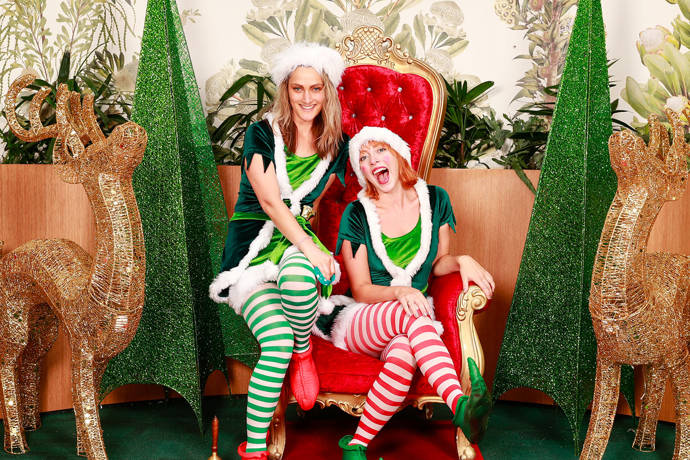 Two female elves sitting on Santa's chair